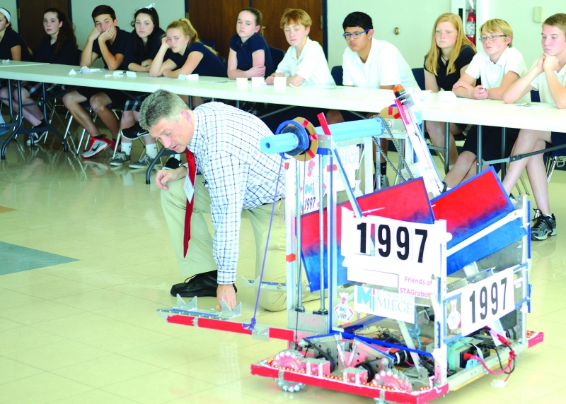 Eighth Graders learning about Bishop Miege's new Project Lead the Way, Engineering, program were treated to a demonstration of the robot designed by students in the robotics program. Scott Anderson, head of Bishop Miege Engineering Department, explained the mechanics of the robot.