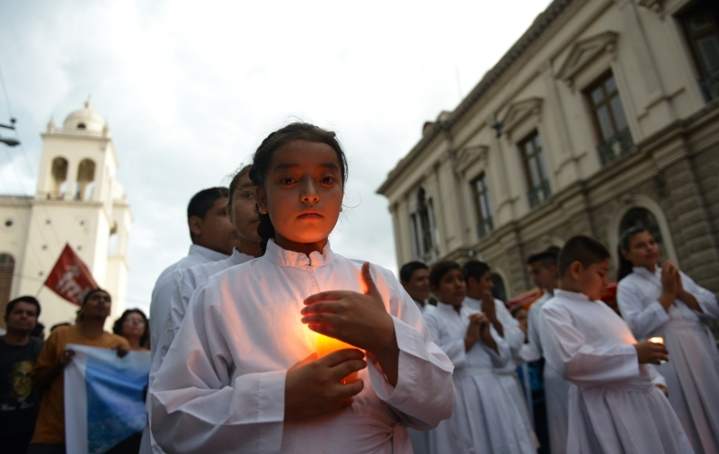 Young people hold candles as they proceed to the Divine Savior of the World square in San Salvador May 22, the day before the beatification of Salvadoran Archbishop Oscar Romero. CNS photo by Lissette Lemus.