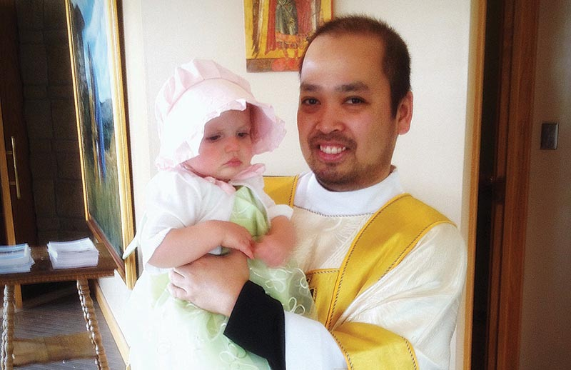 Deacon Jonathan Dizon stands with his goddaughter, Rebekah  Marie Serio, this Easter at  the  St. Lawrence Catholic Campus Center in Lawrence. He will be ordained to the priesthood in May. Photo courtesy of Kati Serio.