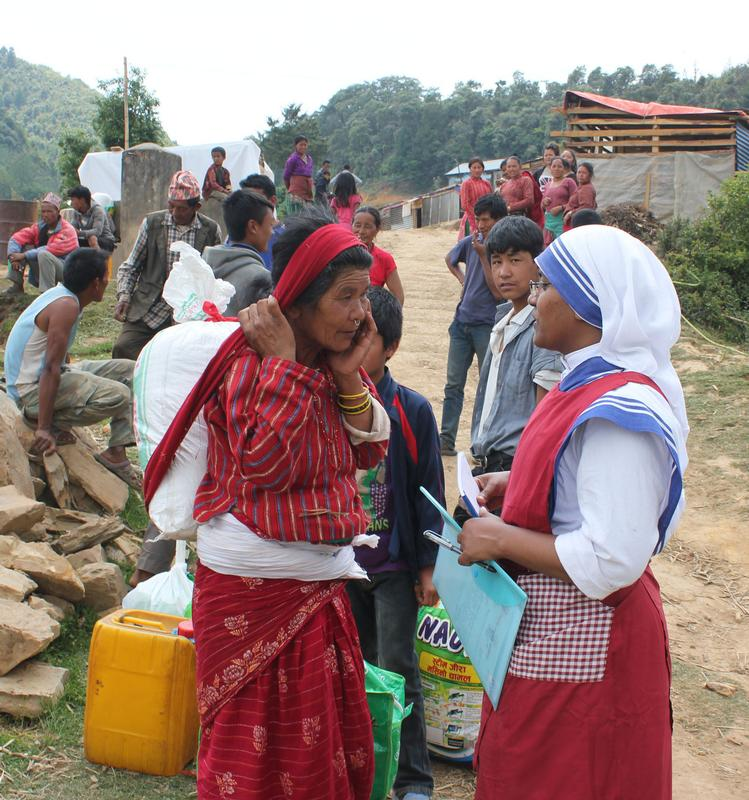 Sister Marica, a member of the Missionaries of Charity, chats with an elderly woman carrying earthquake relief material in the mountains overlooking Kathmandu Valley May 16 in Nepal. CNS photo by Anto Akkara.