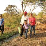 Luis (far left), Jaime, Angel and Reina gather water near their home in Honduras. Reina's life was thrown into chaos when her husband Luis died in a motorcycle crash. Thanks to Randy and Pam Brown, who sponsor Luis and Angel through Unbound, Reina was able to survive the tough times. She has since married Jaime.