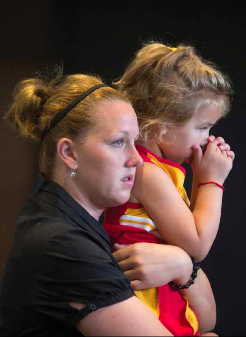 Erin Duvall, a member of St. Patrick Parish in Kansas City, Kan., holds her daughter Riley at last year's Mass of Innocents at Savior Pastoral Center. This year's Mass of Innocents will be celebrated on Oct. 20.