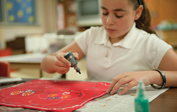 Holy Name seventh-grader Emina Struga works on her Day of the Dead artwork on Oct. 28. Students K-8 created a colorful array of projects to decorate the Kansas City, Kan., school's halls and an altar for the Day of the Dead.