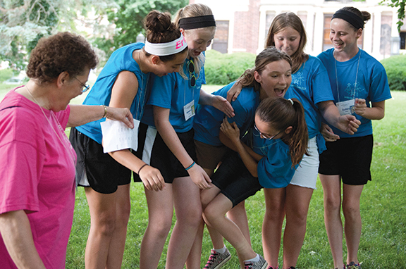 From left, Sister Rosann Eckart, OSB, offers guidance as campers line up according to birth month without stepping off a beam. Lifting Emily Chmidling of Immaculate Conception-St. Joseph Church, Leavenworth, across to her correct spot are, from left, Kaley Coffman of Sacred Heart of Jesus Parish, Shawnee; Veronica Dervin of St. Joseph Parish, Shawnee; Maegan Koch of St. Patrick Parish, Corning; Erin Dulac of Sacred Heart Parish, Atchison; and Sydney Howell of Sacred Heart Parish, Leavenworth.