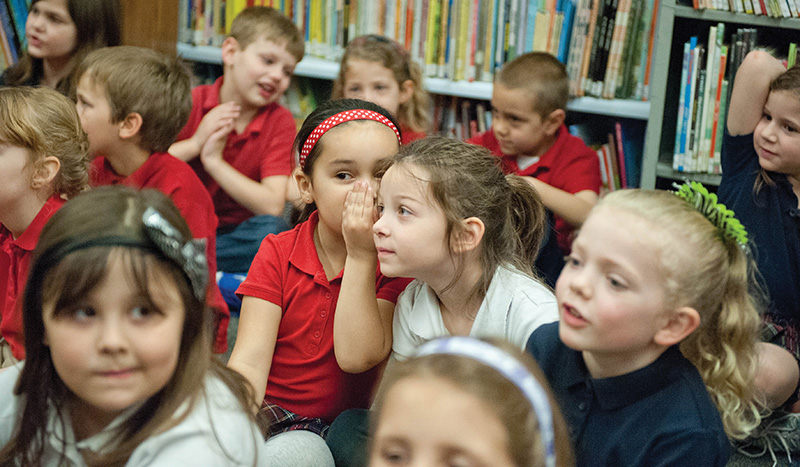 At Mater Dei School, kindergartner Lydia Dennis whispers to Finley Smith during story time in the library. Support for schools takes up a significant percentage of parish income, but parents and other parishioners are willing to make the investment in their children.