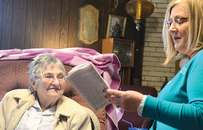Hospice patient Bernice Stirton, left, looks forward to visits from Saint Jude Hospice volunteer coordinator Shawn Gigstad and time spent together reading inspirational stories from Guideposts magazine. Photo by Jill Ragar Esfeld.