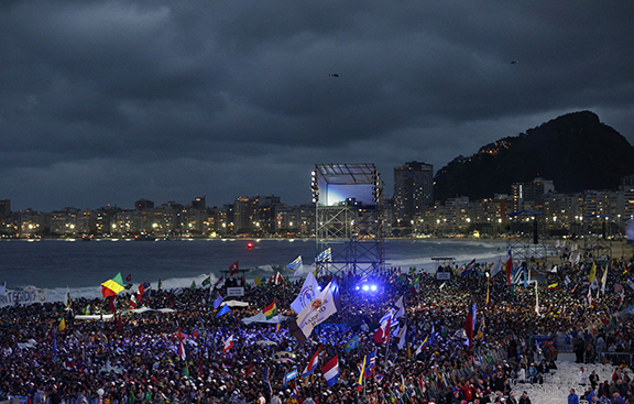 Pilgrims wait for the arrival of Pope Francis at the World Youth Day welcome ceremony on Copacabana beach in Rio de Janeiro July 25. (CNS photo/Paul Haring) (July 26, 2013) See POPE-COPACABANA July 26, 2013, and POPE-BEACHJAM July 26, 2013.