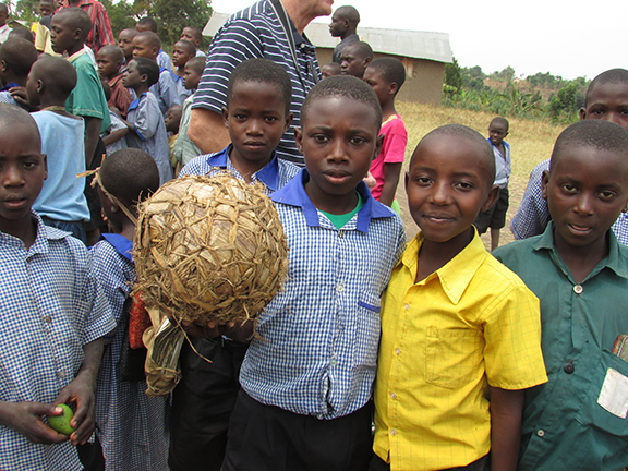 The boys at St. Charles Primary School in Kyakadali proudly display their homemade soccer ball to their guests from the United States. The ball is made from banana leaves.