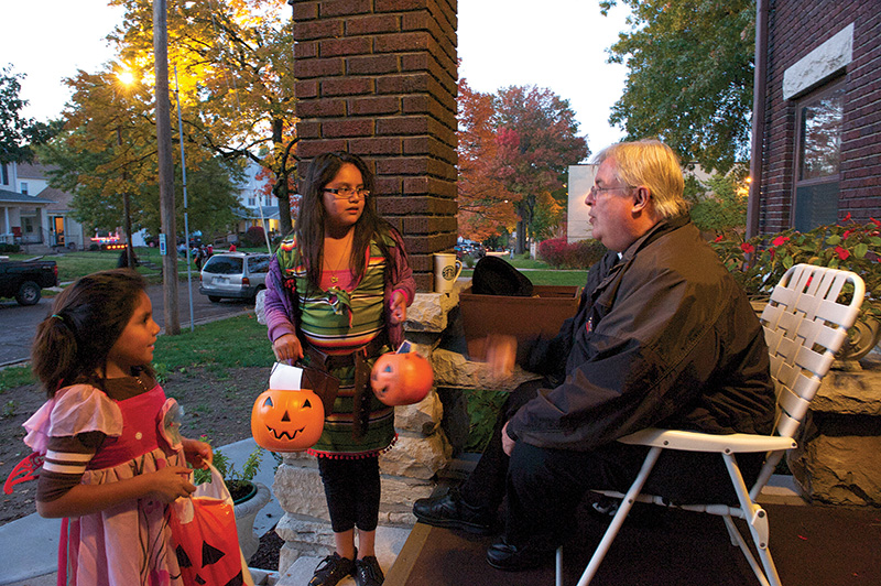 Father Harry Schneider passes out candy last Halloween on the front porch of the cathedral rectory. Halloween is a big social event in the cathedral neighborhood as hundreds of costumed children roam the streets. Photo by Jessica Langdon.