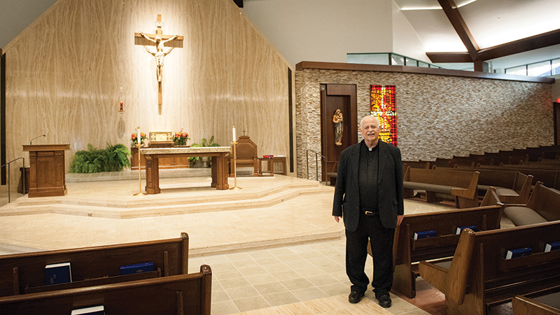 Father Charles McGlinn, pastor of Curé of Ars Parish in Leawood, stands near the renovated sanctuary. The top-to-bottom renovation includes new pews, flooring, lighting, heating, air conditioning, sound system, choir area, paint and Stations of the Cross. Photo by Lori Habiger.