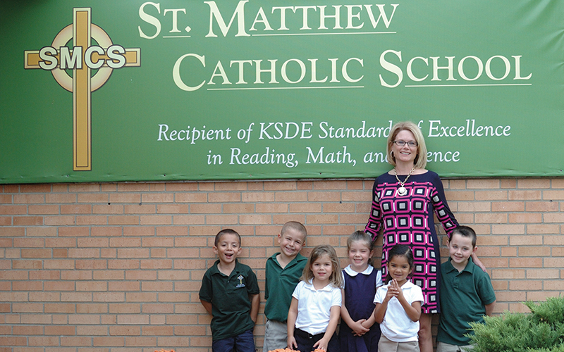 LEAVEN PHOTO BY JILL RAGAR ESFELD Principal Heather Huscher stands with kindergartners Jordan Barranco, Nigel Garcia, Katalina Uhl, Lilly Charvat, Ava Rogers, and Payton Reinecke outside St. Matthew in Topeka, recipient of the 2014 Archbishop Joseph F. Naumann Catholic Education Foundation School of Excellence Award.