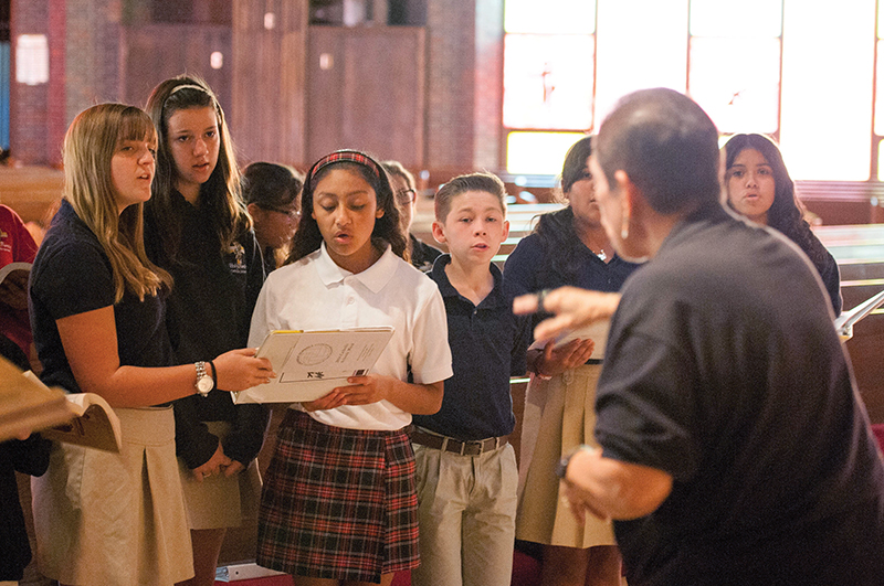 Left to right, Holy Family students Karina Short, Victoria Burghart, Lizeth Ruiz, Marisol Marcelo, Isabel Hudgins (obscured), Gabe Smith, Lesley Ayala (obscured) and Nuvia Valadez work on a song under the direction of their choir instructor Rita Bennett.