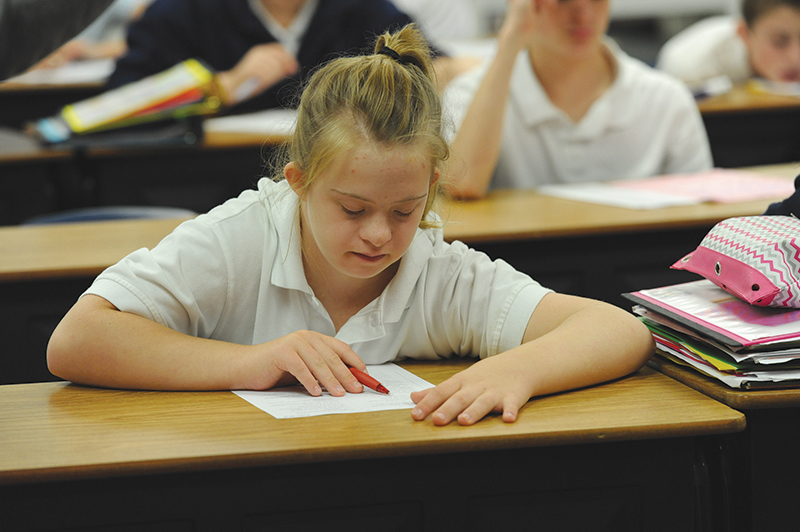Kathryn Embry, an eighth-grader at Nativity Parish School, reads a passage in Barb Burgoon's religion class. Kathryn and her classmates are preparing for confirmation.