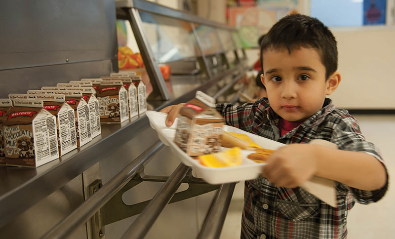 Preschooler Benito Guerrero of Holy Name School in Kansas City, Kansas, tops off his lunch selections with a carton of chocolate milk. Thousands of children like Benito might now have the opportunity to attend Catholic schools thanks to eligible businesses that participate in a new tax credit program introduced by the state of Kansas — but the clock is ticking. To see how you can help, see story below.