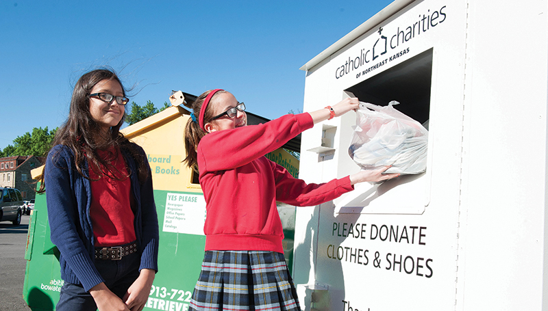 Alice Brandt, left, and Lauren McFarlane, fifth-graders at St. Agnes School in Roeland Park, drop off a donation at the Catholic Charities bin on the parish grounds.