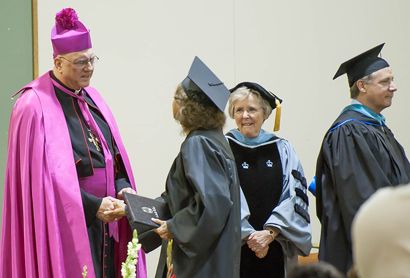 Archbishop Joseph F. Naumann congratulates a graduate of Donnelly College at the graduation ceremony May 9 at the Jack Reardon Civic Center in Kansas City, Kansas, as Sister Anne Shepard, prioress of the Benedictine Sisters in Atchison, looks on. Photo by Jessica Langdon.