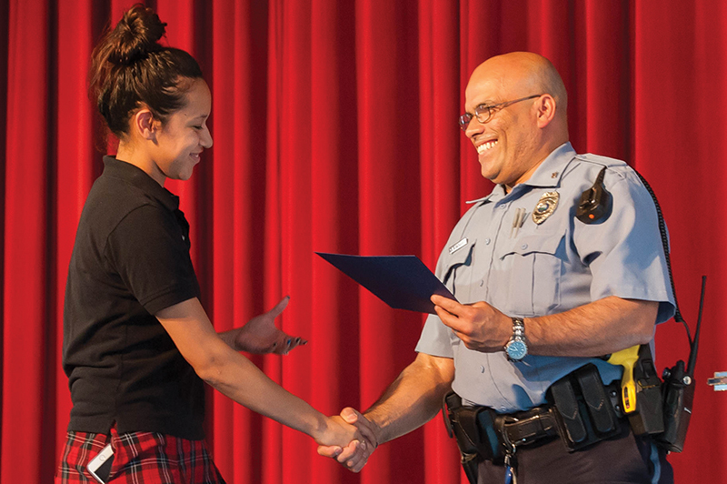 Officer Santiago Vasquez, Bishop Ward student resource officer and a senior master patrolman with the Kansas City, Kansas, Police Department congratulates senior Yusmayra Calderon on completing Ward's Junior Police Academy program. Photo by Jessica Langdon.