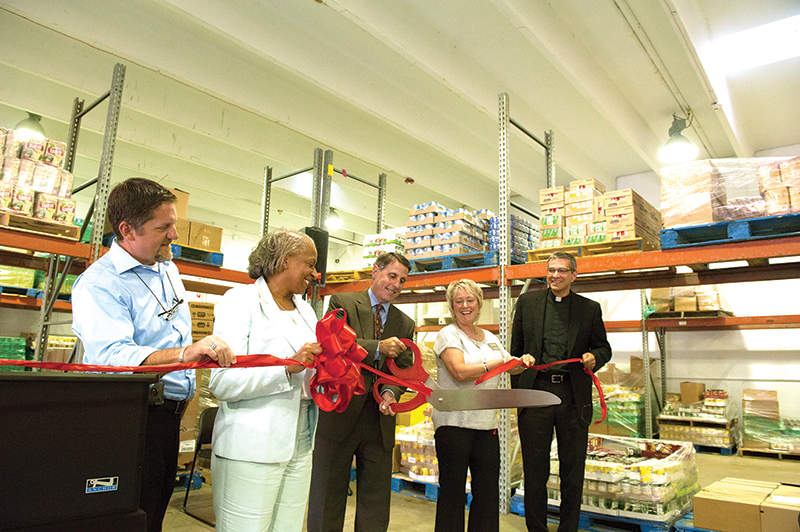 Ken Williams, center, president/CEO of Catholic Charities of Northeast Kansas, does the honors of cutting the ribbon at the new Hope Distribution Center in Kansas City, Kansas. Also participating in the ceremony on Aug. 14 are, from left, Mark Holland, mayor/CEO of the Unified Government of Wyandotte County/Kansas City, Kansas; Valerie Nicholson-Watson, president and CEO of Harvesters; Kim Brabits, vice president of program operations of Catholic Charities of Northeast Kansas; and Father Brian Schieber, pastor of St. Michael the Archangel Parish in Leawood.