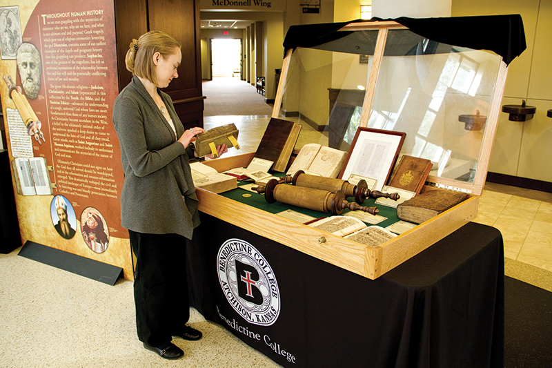 "Benedictine senior and exhibit docent Claire Willms views some of the unique items at the Atchison college's ""Wisdom of the Ages"" exhibition. Items will be on display inside the Laughlin Rotunda in the Ferrell Academic Center on Benedictine's campus from Oct. 13 - 19 and again from Nov. 8 – 14."