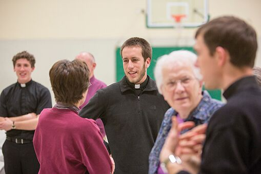 Chris McCoy, nSJ (center), visits with the parishioners at the Cathedral of St. Peter. McCoy and two other Jesuit novices provided a variety of spiritual services in the area during their six weeks in the archdiocese.