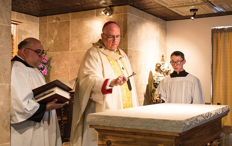 Archbishop Joseph F. Naumann blessed the altar with holy water after placing a cylindrical limestone plug containing a relic of St. Frances Xavier Cabrini in its center. Later, he also anointed the altar with chrism. He was assisted in the rite and the Mass by archdiocesan consultant for liturgy Michael Podrebarac (left) and acolyte Val Lobatos, a member of the Cathedral of St. Peter Parish in Kansas City, Kansas.  Photo by Joe Bollig.