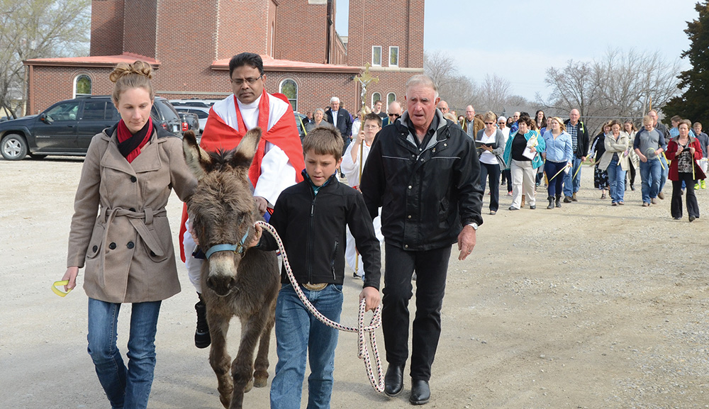 Dianna Welsh, left, leads a donkey ridden by Father Lazar Carasala, with help from Colby Weishaar, as Bob Weisharr walks alongside them as a spotter outside Immaculate Conception Church in Valley Falls on March 29. The Weishaars found the donkey Father Carasala rode at Immaculate Conception and at St. Joseph Church in Nortonville during Palm Sunday processions, reenacting Jesus' entrance into Jerusalem.