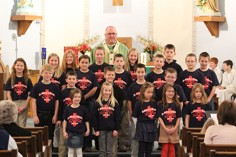 Archbishop Joseph F. Naumann kicked off Catholic Schools Week by celebrating the 125th anniversary of St. Michael School in Axtell. Above, the archbishop stands with the school's student body.