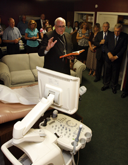 Archbishop Joseph F. Naumann blesses the new 3-D sonogram machine at the Wyandotte Pregnancy Clinic on June 29.