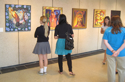Visitors to Savior Pastoral Center check out the new art exhibit adorning the center's walls.