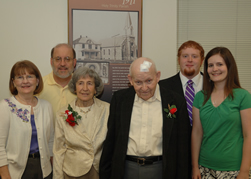 Leaven photo by Jill Ragar Esfeld Patricia and Leonard Haefele (seated) pose with their daughter Carol and her husband Joe Testa (standing left) and their granddaughter Joanna and her husband Tyler Johnson in front of a picture of the Holy Trinity Church, where they were all married. Leonard Haefele's parents Ella Marie and Louis Haefele were also married there.