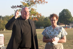 Father Pete O'Sullivan, pastor of Christ the King Parish in Topeka, blesses the ground where a rosary garden in honor of Aubry Williams, will be built. Aubry's mother, Mary Franz, looks on as her daughter's dream of a prayer garden for the parish takes shape.
