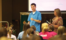 Joe White shares his story with teens at Sacred Heart Parish in Tonganoxie on Oct. 5. His longtime friend Abbie Eli holds a Bible, from which White shares several Scripture passages. Joe was a high school student in 2006 when he jumped from a moving vehicle attempting a stunt. He suffered a brain injury and now shares his story of bad decisions, overcoming obstacles and finding faith with young people. By Jessica Langdon.