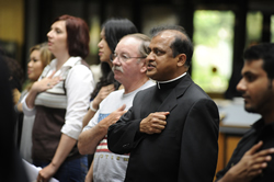 Father Arul Carasala recites the Pledge of Allegiance at a ceremony in which he became a citizen of the United States on May 20 in the state capital. Father Carasala is pastor of St. Vincent de Paul Parish in Onaga, St. Patrick Parish in Corning, St. Bede Parish in Kelly and St. Columbkille Parish in Blaine.