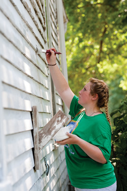 Shaleigh Yearsley, a member of St. Joseph Parish in Shawnee, applies a fresh coat of white paint to the same home, which belongs to Marcia Canaday. Although Canaday decided against applying for assistance because she believed there were others who needed the help more, her 11-year-old daughter Ruth sent in the application anyway, and the house was chosen for repairs.