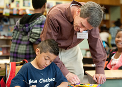 Brad Grabs, director of The Learning Club after-school program at Blessed Sacrament in Kansas City, Kan., works with second-grader Erick Gutierrez. TLC celebrated its 10th anniversary in February.