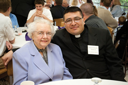 Leaven photo by Joe Bollig Louise Naumann and Deacon Oswaldo Sandoval take a break from the annual Chrism Mass lunch April 3 at Savior Pastoral Center to pose for a photo. After Louise Naumann stopped driving, Deacon Sandoval stepped up and volunteered to help take her shopping and to her doctor and dentist appointments.