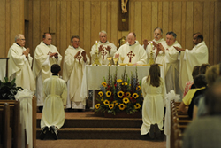 Father Pat Sullivan, at the time parochial administrator of St. Joseph in Lillis, celebrates Mass with several former pastors of the parish. Concelebrating with Father Sullivan are: (from left) Father Carl Dekat, Father David Smith, Father George Seuferling, Father Bob Hasenkamp, Father Mike Stubbs (partially blocked), Father Phil Winkelbauer, Father Jim Shaughnessy, and Father Arul Carasala.