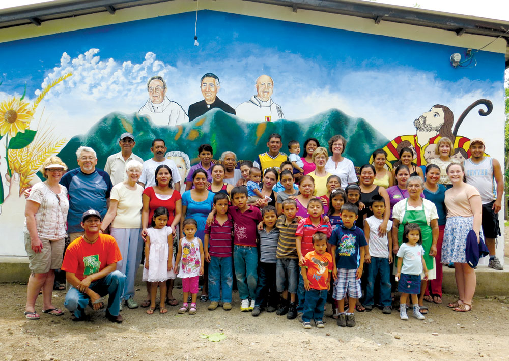 Good Shepherd parishioner Sarah Hotzel cuts the cake celebrating 25 years of solidarity between Good Shepherd Parish in Shawnee and the community of El Buen Pastor in El Salvador.