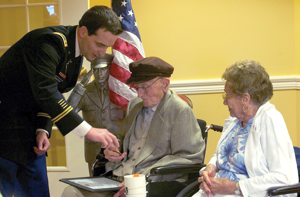 """Leaven photo by Jessica Langdon Maj. Sean C. McCaffery, left, visits with World War II veteran Warren Berg and wife Genevieve in May. Catholic Community Hospice arranged the ceremony to thank Berg for his service to his country. Berg died in June. Catholic Community Hospice honors its veterans at the end of their lives, providing a """"hero's welcome"""" and offering a chance for the veterans to share their stories with hospice staff and local veterans."""