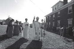 Archbishop Joseph F. Naumann blesses the ground where the new monastery for the Community of the Lamb, a group of Dominican religious, will be built. Assisting the archbishop is Little Brother Clement, an acolyte in the order. Behind them are Little Sisters Bénédicte (far left), Aude (partiality obscured), Lucie, Alma, and Msgr. Gary Applegate, master of ceremonies.