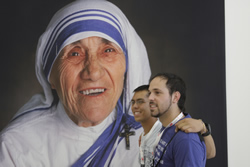 Archdiocesan seminarian Evan Tinker (left) and Mikey Needleman, a member of Holy Spirit Parish in Overland Park, pose in front of a giant image of Mother Teresa. A group from Mother Teresa of Calcutta Parish in Topeka spent a day volunteering with Mother Teresa's  Missionaries of Charity.