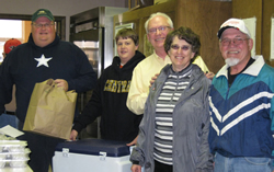 Photo by Laurie Ghigliotti Dan Hennigh (left), Jake Hennigh, Galen Pruett, and Judy and Jerome Walters prepare to deliver hot meals to shut-ins in Atchison through the Loaves and Fishes program.