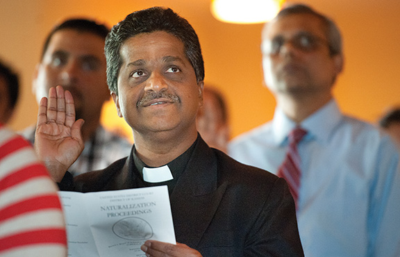 """Father Marianand Mendem, pastor of St. Francis Xavier Parish in Burlington, St. Patrick in Emerald, St. Joseph in Waverly, and St. Teresa in Westphalia raises his hand and swears to """"bear true faith and allegiance"""" to the United States as he becomes an American citizen. Leaven photo by Lori Wood Habiger"""