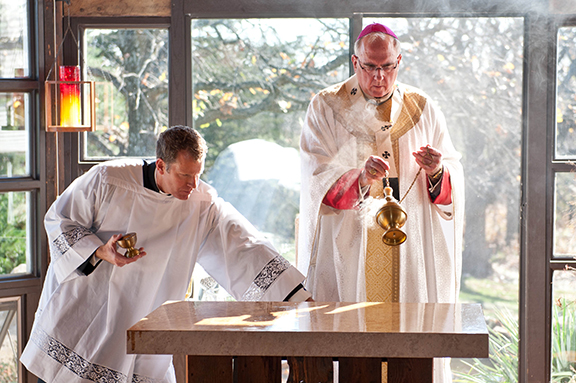 LEAVEN PHOTO BY JOE BOLLIG Archbishop Joseph F. Naumann, with assistance from master of ceremonies Father John Riley, incenses the new altar at Christ's Peace House of Prayer on Oct. 29, just in time for the Year of Faith.