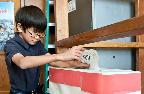 Khoa Nguyen, a fifth-grader at John Paul II School in Overland Park, casts his ballot in a school-wide election to determine which service project the school will complete in February.