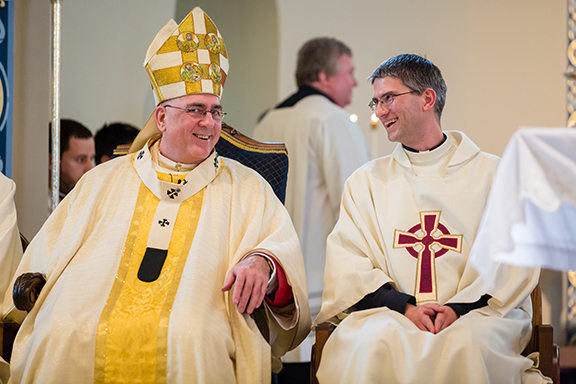 PHOTOS COURTESY OF BELLTOWER PHOTO Above, Archbishop Joseph F. Naumann and Deacon Lawrence Bowers share a laugh during Bower's ordination to the transitional diaconate on Nov. 10 at Immaculate Conception Parish in St. Marys.