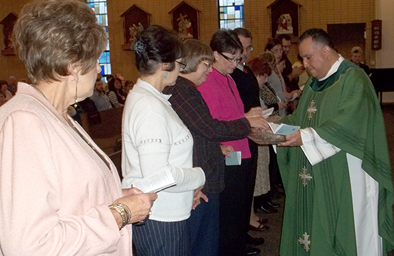 PHOTO COURTESY OF THE HOLY NAME SOCIETY Father John Torrez blesses medallions and buttons and presents them to new members of the Holy Name Society. They are, from left, Ruth Pfiefer, treasurer; Nancy Cariglio; Joyce Harding, president; Quinta Schwarzenberger, counselor; Tom Schwarzenberger, counselor; and Trisha Kirkbride, secretary.