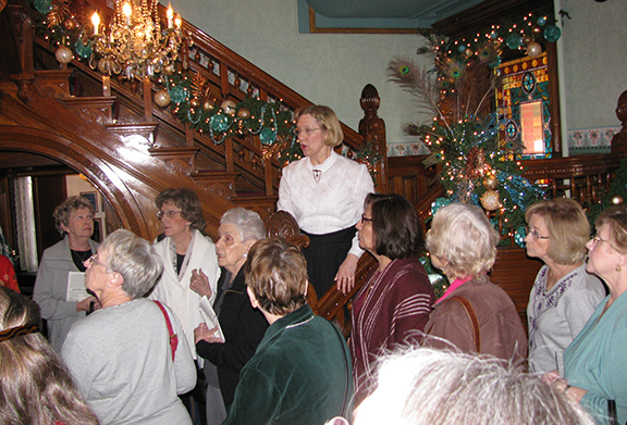 LEAVEN PHOTO BY SHEILA MYERS Volunteer Bernadette Soptick leads a tour of Holy Spirit parishioners in the foyer of the original home that became the Strawberry Hill Museum. During the holidays, Soptick leads tours dressed as Emma Cruise McFadden, daughter of Margaret Cruise Scroggs, the original mistress of the house.
