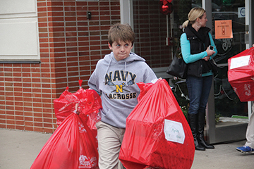 PHOTO BY HEATHER SULLIVAN Tate Rowland, an eighth-grader at St. Ann School in Prairie Village, hauls bags of gifts to load in a truck to deliver for Christmas to children in the foster care system. Working with the Red Bag Program has been an Advent tradition at St. Ann for decades.