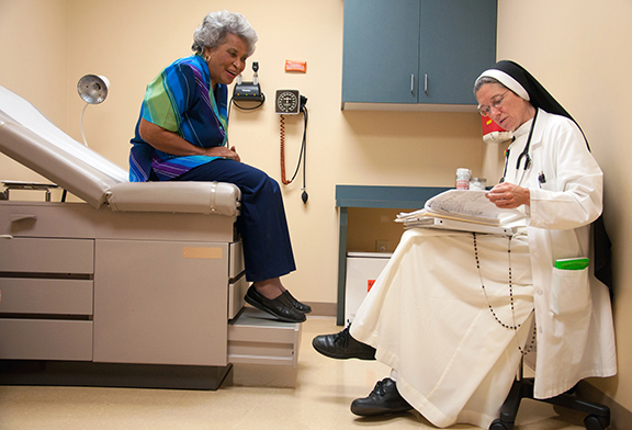 "CNS PHOTO/THERESA LAURENCE, TENNESSEE REGISTER Dominican Sister Mary Diana Dreger, a physician, sees a patient at St. Thomas Family Health Center South in Nashville, Tenn., in this file photo. The Health and Human Services contraceptive mandate requires all employers, including most Catholic employers, to provide employees with free health insurance coverage of contraceptives, including some abortion-inducing drugs, and sterilization even if the employer is morally opposed to doing so. Although the Obama administration has announced an accommodation for religious institutions such as hospitals, the Catholic Health Association rejected the administration's accommodation for religious employers. The CHA said the suggestion to have insurers pick up the costs would be ""unduly cumbersome"" and ""unlikely to adequately meet the religious liberty concerns."""